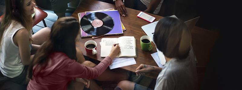 Tonårstjejer runt ett soffbord med kaffe och anteckningsblock. En LP-skiva ligger på bordet.