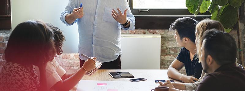Foto av fem personer som sitter vid ett bord vända mot en man vid en whiteboard som berättar om något.